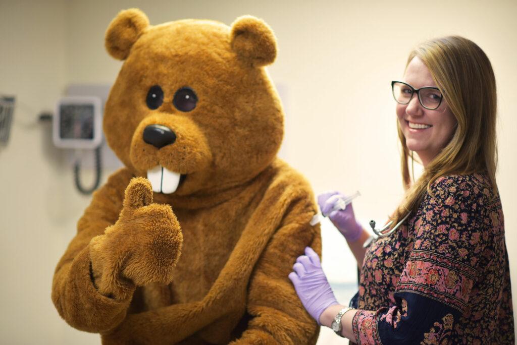 Champlain College mascot, Chauncey T. Beaver, getting a free flu shot