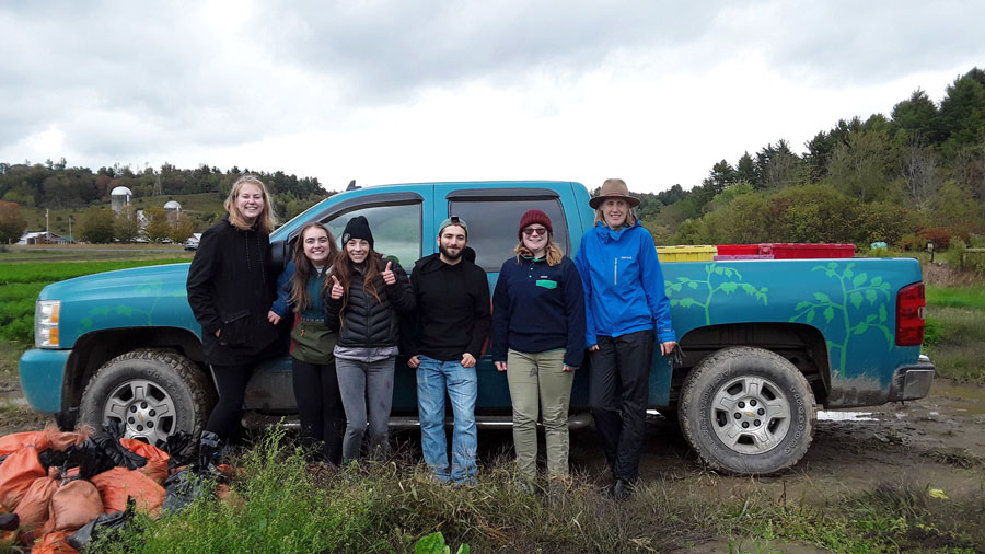 Students from the Center for Service & Sustainability pose in front of a truck after harvesting kale.