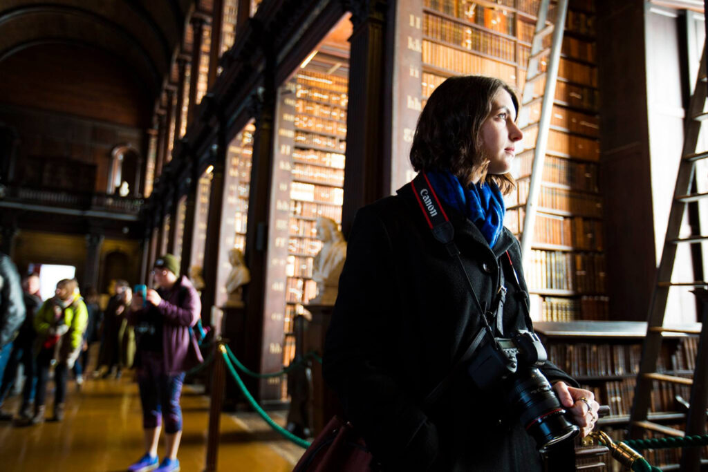 Student poses with a camera at Trinity University's library while studying abroad in Dublin.