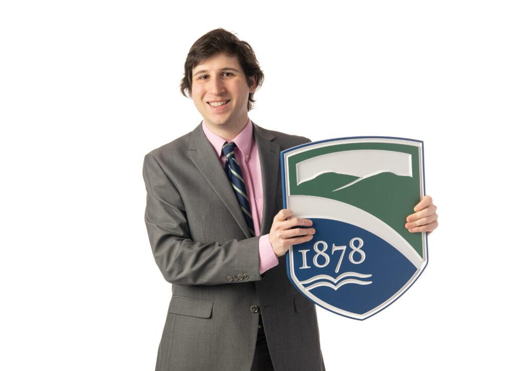 Professor David Kopec holds up Champlain College's crest.